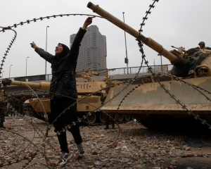 An opposition demonstrator gestures in front of tanks on the frontline near Tahrir Square in Cairo